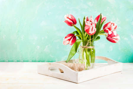 Spring concept. Flowers tulips in a glass mason jar, on a light blue and wooden white background. Copy space Stock Photo