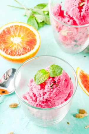 Ice cream, blood orange and cardamom sorbet, with fresh oranges and mint,  light blue background, copy space 写真素材 - 94942588