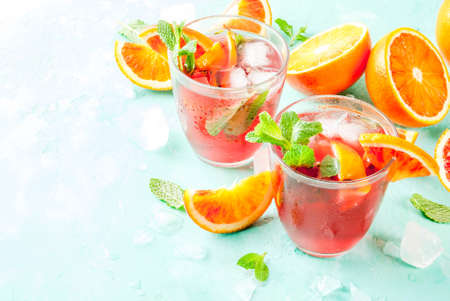 Summer cold drink, blood orange mint cocktail - mimosa, mojito or sangria,  light blue background, copy space