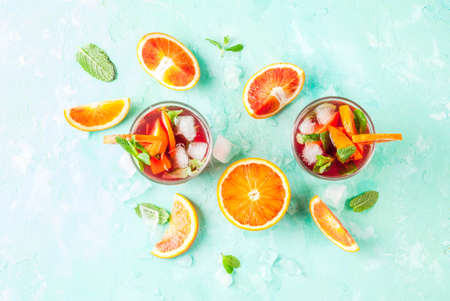 Summer cold drink, blood orange mint cocktail - mimosa, mojito or sangria,  light blue background, copy space top view
