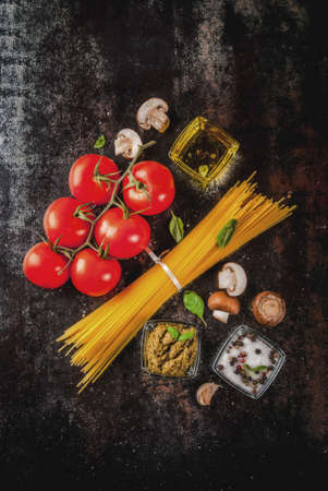 Food background, ingredients for cooking dinner.  Pasta spaghetti, vegetables, sauces and spices,dark rusty background copy space top view