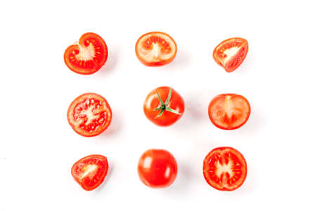 Fresh vegetables, raw whole and cut tomatoes, on white background, isolation copy space  top view Reklamní fotografie