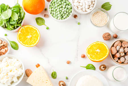 Healthy food concept. Set of food rich in calcium - dairy and vegan Ca products, white marble background top view copy space frame
