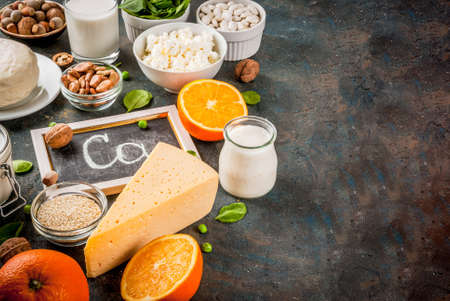 Healthy food concept. Set of food rich in calcium - dairy and vegan Ca products, dark blue background copy space Stok Fotoğraf