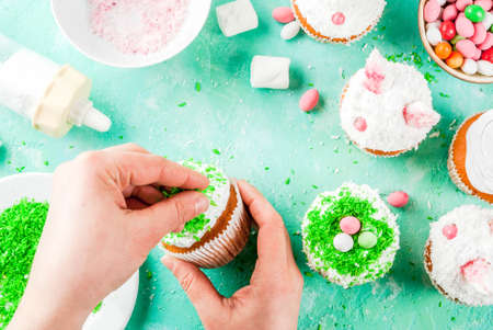 Making easter cupcakes, person decorate cakes with bunny ears and candy eggs, copy space  top view, girls hands in picture Stock Photo
