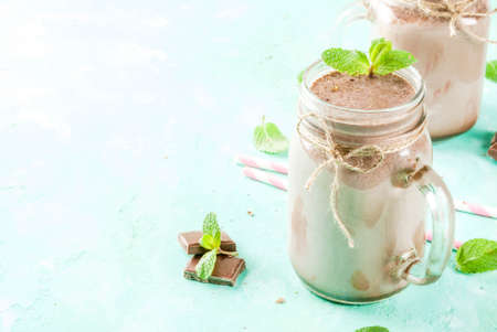 Chocolate smoothie or milkshake with mint and straw, in mason jar on light blue background, copy space