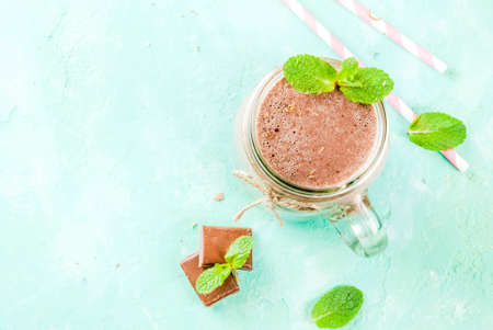Chocolate smoothie or milkshake with mint and straw, in mason jar on light blue background, copy space top view