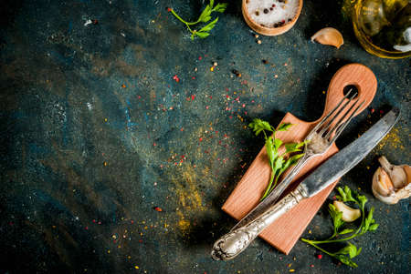 Cooking foor concept, spices, herb and oil for preparing dinner, with cutting board, table knife and fork, copy space top view