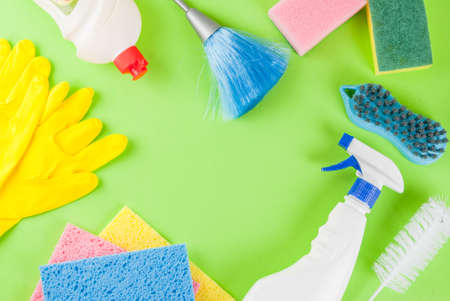 Spring cleaning concept with supplies, house cleaning products pile. Household chore concept, on green background top view copy space frame