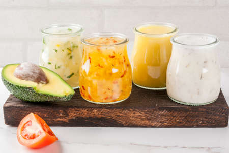 Set of classic salad dressings - honey mustard, ranch, vinaigrette, lemon & olive oil,  on white marble table, copy space Фото со стока