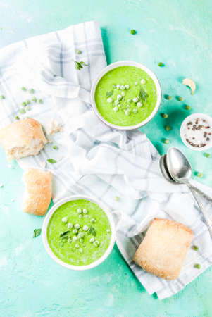 Green pea soup with fresh bread on light blue concrete table, copy space top view