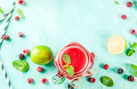 Healthy fresh fruit smoothie with ingredients on light blue concrete table, copy space top view