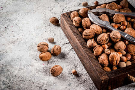 Various nuts and nutcracker in wooden box. On rustic grey stone table, copy space