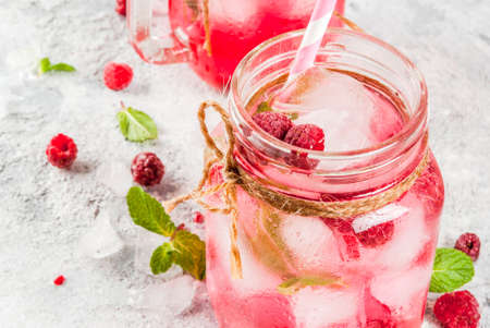 Cold summer drink, Raspberry Sangria, Lemonade or Mojito with fresh Raspberry and syrup, mint leaves, on grey stone background copy space