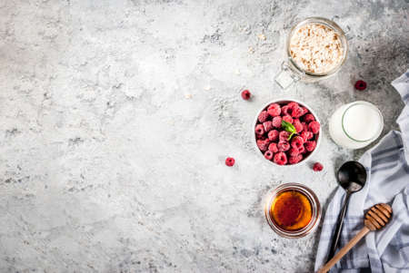 Raw ingredients for summer healthy breakfast, cereals (oats), fresh Raspberry, mint leaves, yoghurt, honey, on light concrete background, top view, copy space