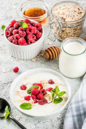 Raw ingredients for summer healthy breakfast, cereals (oats), fresh Raspberry, mint leaves, yoghurt, honey, on light concrete background, copy space