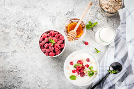Raw ingredients for summer healthy breakfast, cereals (oats), fresh Raspberry, mint leaves, yoghurt, honey, on light concrete background, copy space top view Banque d'images