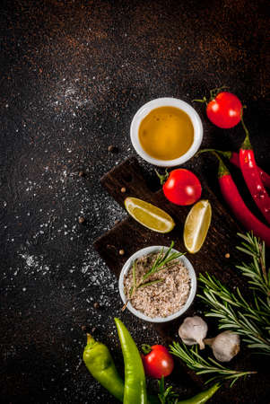 Food cooking ingredient, olive oil, herbs and spices, dark rusty background top view copy space