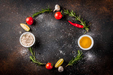 Food cooking ingredient, olive oil, herbs and spices, dark rusty background top view copy space frame Banque d'images