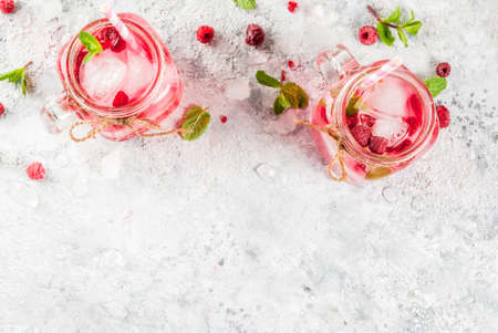 Cold summer drink, Raspberry Sangria, Lemonade or Mojito with fresh Raspberry and syrup, mint leaves, on grey stone background copy space top view
