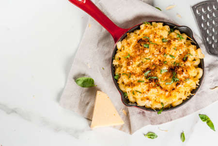 Mac and cheese, american style macaroni pasta with cheesy sauce and crunchy breadcrumbs topping, in portioned pan, white marble table, copy space top view