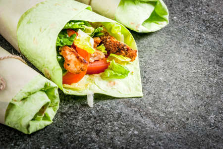 Mexican food. Healthy eating. Wrap sandwich: green lavash tortillas with spinach, fried chicken, fresh greens salad, tomatoes, yoghurt sauce. Black dark stone table. Copy space