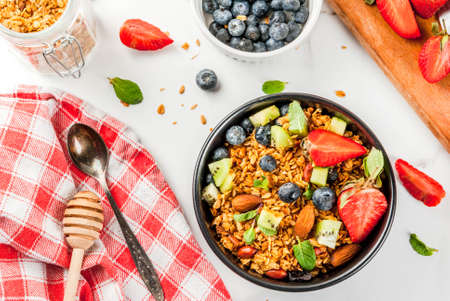 Healthy breakfast with muesli or granola with nuts and fresh berries and fruits - strawberry, blueberry, kiwi, on white table, copy space top view Stock Photo