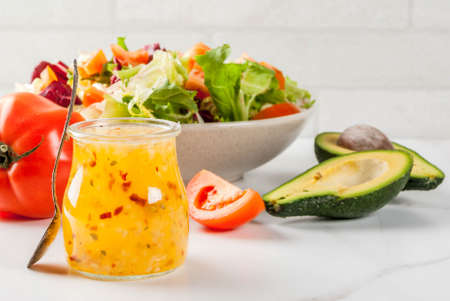 Classic Italian vinaigrette salad dressing, with fresh vegetables on white marble table, copy space Stok Fotoğraf