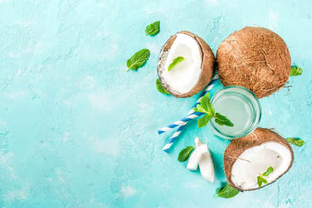 Healthy food concept.  Fresh Organic Coconut Water with coconuts, ice cubes and mint, on light blue background, copy space top view Stok Fotoğraf