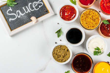 Set of different sauces - ketchup, mayonnaise, barbecue, soy, teriyaki, mustard, grain hills, pesto, adzhika, chutney, tkemali, pomegranate sauce on white marble background. Top view copy space