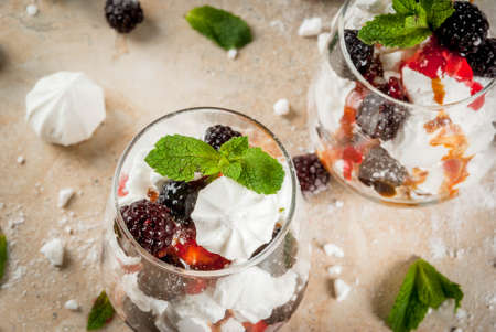 Traditional English dessert. Eton mess - whipped cream, meringue, fresh blackberries, sauce and caramel. In serving glasses on a light stone table. Copy space Stok Fotoğraf
