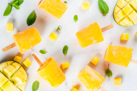 Ice cream, popsicles. Organic dietary foods, desserts. Frozen mango smoothie, with mint leaves and fresh mango fruit, on a white marble table. Copy space top view Stok Fotoğraf