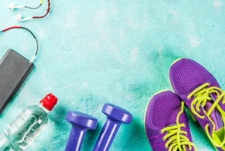 Sports, fitness concept. Running sneakers, water bottle, headphones, dumbbells, smartphone, on a light blue background top view copy space Stok Fotoğraf