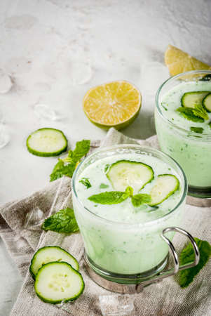 Summer food. Refreshing dishes. Cold soup of cucumber, avocado, with herbs and mint. With serving glasses, with slices of cucumber. On a white concrete table, with ingredients. Copy space Stock Photo