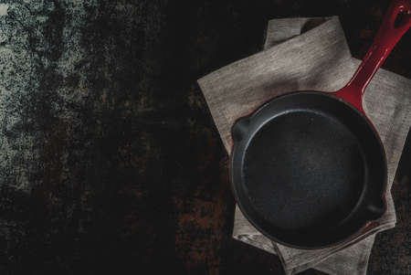 Dark rusty culinary background with empty black pan, top view copy space