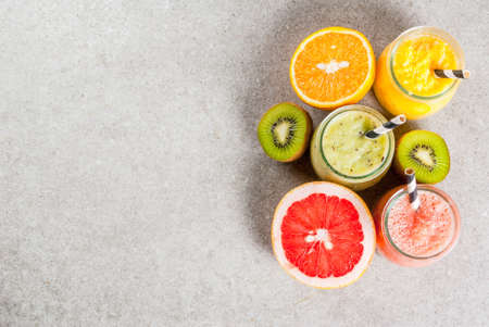 Detox organic diet drinks, homemade tropical smoothies - kiwi, orange, grapefruit, in portioned jars, with ingredients, on a gray stone table. Copy space top view Stok Fotoğraf