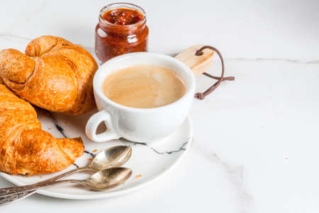 Homemade continental breakfast, coffee croissants. jam on white marble table, copy space