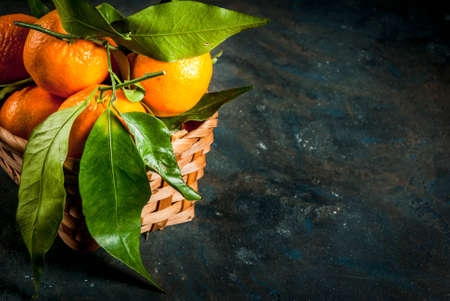 Fresh raw organic Tangerines with green leaves in little basket on dark concrete stone background, copy space Stok Fotoğraf