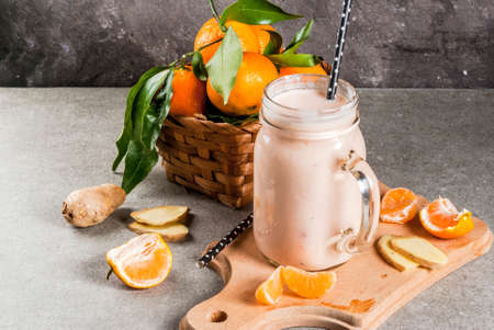 Tangerine Smoothie with Ginger in mason jar, with fresh raw Tangerines, in grey stone background copy space