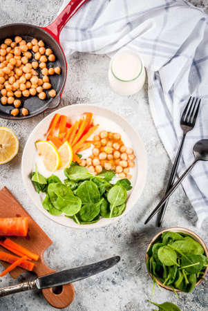 Modern vegan food, savory yogurt bowl with beans, chickpeas, spinach, spicy carrots, lemon, Gray stone background, copy space top view Stok Fotoğraf