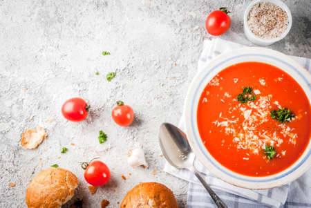 Tomato soup, Gazpacho in white bowl on grey stone background, with ingredients Top view. Copy space