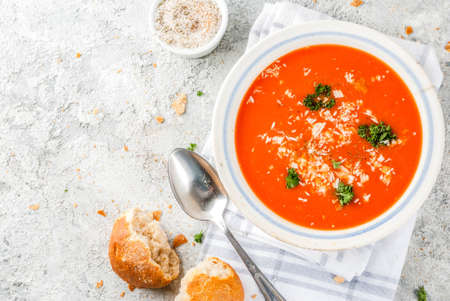Tomato soup, Gazpacho in white bowl on grey stone background, with ingredients  Copy space top view Stockfoto