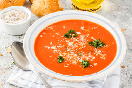 Tomato soup, Gazpacho in white bowl on grey stone background, with ingredients  Copy space