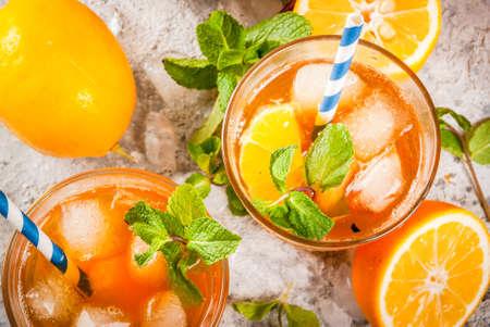 冷たい夏の飲み物。灰色の石の背景にレモンとミントとアイスティー。 スペースの上のビューをコピーする