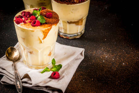Three portioned glass with Italian dessert Tiramisu, with mint and raspberries, on dark rusty background.  Copy space Stok Fotoğraf