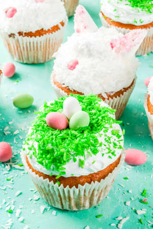 Easter cupcakes with bunny ears and candy eggs, copy space