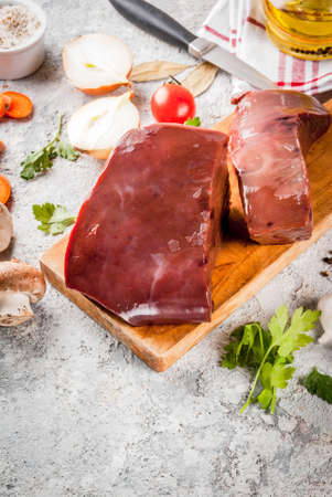 Raw beef liver with spices, herbs and vegetables, grey stone table copy space Stock Photo