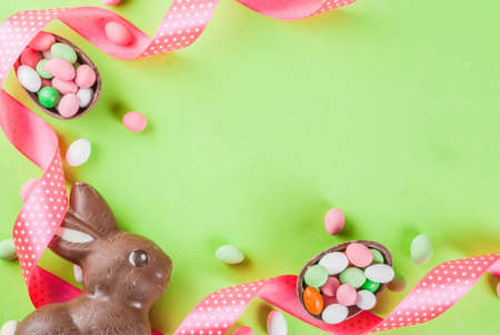 Easter holiday greeting card background, with chocolate easter bunny, candy eggs, quail eggs and festive ribbon, copy space top view Stock Photo