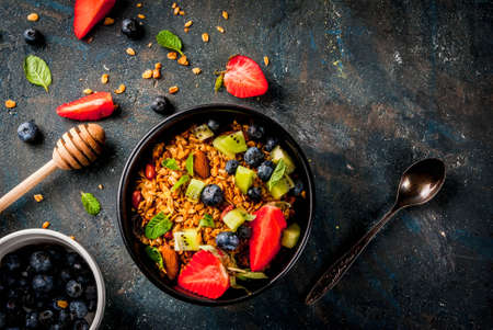 Healthy breakfast with muesli or granola with nuts and fresh berries and fruits - strawberry, blueberry, kiwi, on dark blue table, copy space top view