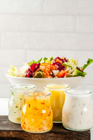 Set of classic salad dressings - honey mustard, ranch, vinaigrette, lemon & olive oil,  on white marble table, copy space Stock Photo